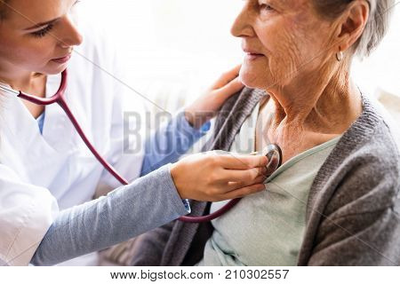 Health visitor and a senior woman during home visit. A nurse or a doctor examining a woman. Close up.