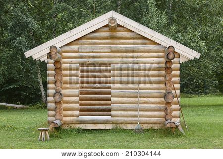 Wooden cabin in the forest under construction. Raw materials. Finland