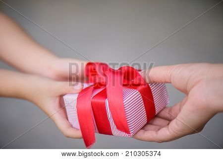 Mother hand giving a gift box to her child. Holidays present christmas childhood and happiness concept