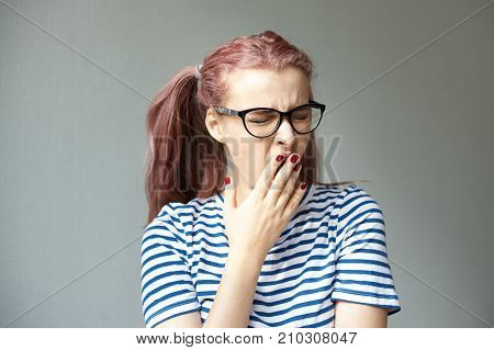 Studio portrait of funny pink haired young woman in stylish eyewear and striped top going to bed feeling sleepy and tired covering mouth while yawning after long active day. Body language