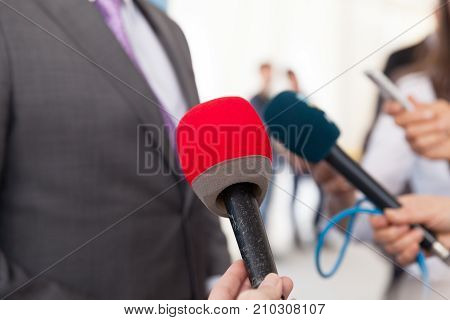 Media or press interview. News conference. Microphone. Journalism.