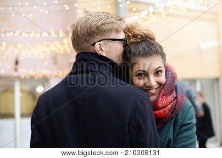 Sweet moment of true love. Romantic young couple in winter clothes cuddling outdoors: Hispanic girl with nose ring and blonde Caucasian guy in eyeglasses hugging on street decorated with light garland