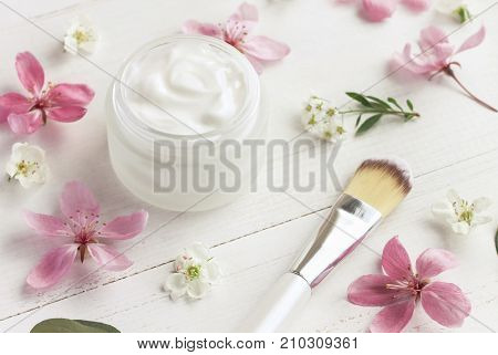Cosmetic jar of facial cream with fresh delicate pink apple blossom white table,feminine soft light and focus.