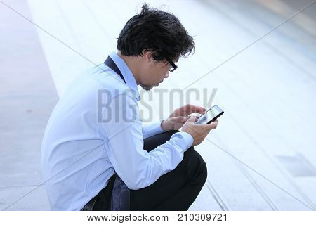 Unemployed young Asian businessman using mobile smart phone find a job. Depressed unemployment business concept.