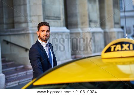 A handsome young businessman getting in to a taxi