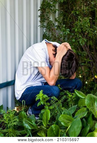 Sad Young Man sit by the Wall outdoor