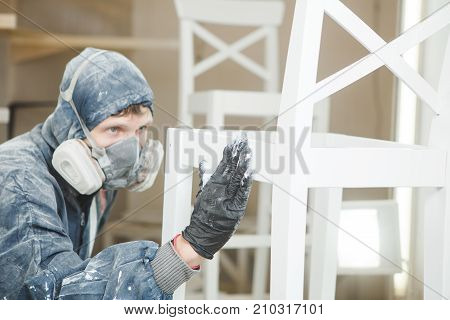 man checks the evenness of the paint application in respiratory mask. Application of flame retardant ensuring fire protection, airless spraying device.
