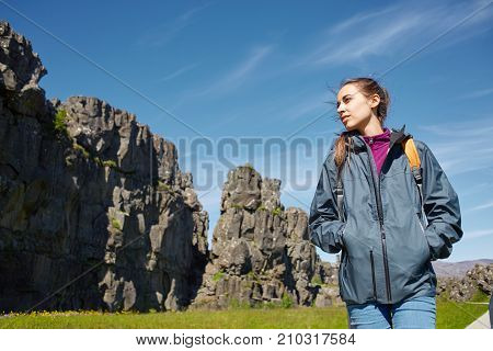 back view of young woman hiker hiking in beautiful mountains. female hiker with small orange packpack black lava rocks background. excursion to the national park Thingvellir in Iceland