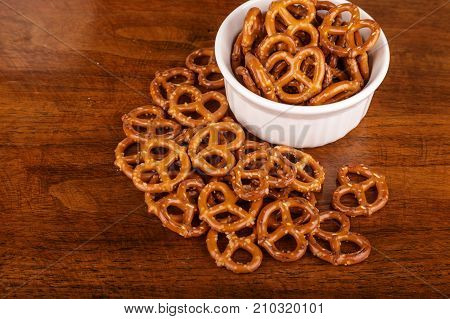 Fresh pretzels in a white bowl and on a wood table
