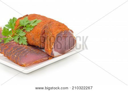 Fragment of a white rectangular dish with partly sliced cured pork tenderloin decorated with parsley twigs closeup on a white background