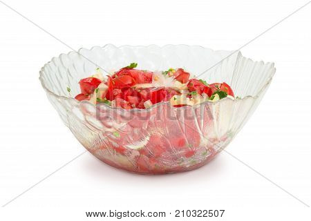 Vegetable salad of the sliced tomatoes white bell peppers onion and potherb in a glass salad bowl on a white background