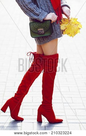 Fashionable woman wearing trendy red high, over the knee suede boots walking in street. Model holding small green textured bag and yellow autumn leafs. Elegant city outfit. Female fashion concept