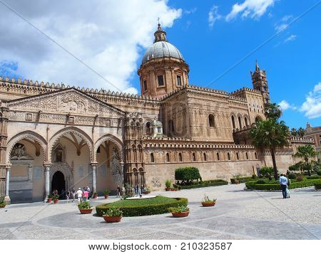 PALERMO ITALY EUROPE on MAY 2016: Medieval cathedral church at square in center of italian city at Sicily with towers and tourists in front of building cloudy blue sky in warm sunny spring day.