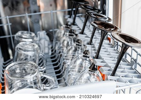 Open dishwasher with clean glass and dishes selective focus Clean glasses after washing in the dishwasher. poster