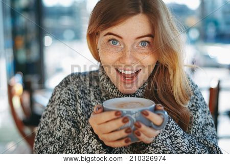Cheerful young woman holding a cup of coffee with open mouth happy. Natural reddish girl with freckles, dressed in soft wool sweater, smiling surprised while holding a big cup of coffee latte.