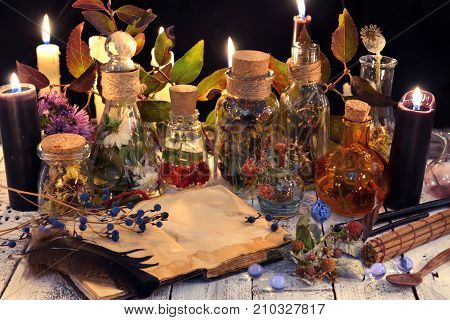 Open book with copy space, herbs and berries, black candle and magic objects on witch table. Occult, esoteric, divination and wicca concept. Alternative medicine and homeopathic vintage background
