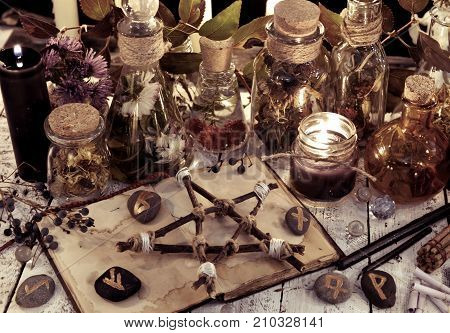 Potion bottles, wooden pentagram, black candles and magic objects on witch table, toned image. Occult, esoteric, divination and wicca concept. Alternative medicine and Halloween vintage background poster