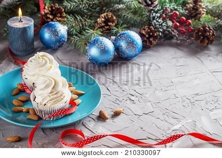 Christmas composition with two muffins candle and holidays decorations with copy space. Christmas and New Year cupcakes decorated for holiday dinner. Christmas dessert.