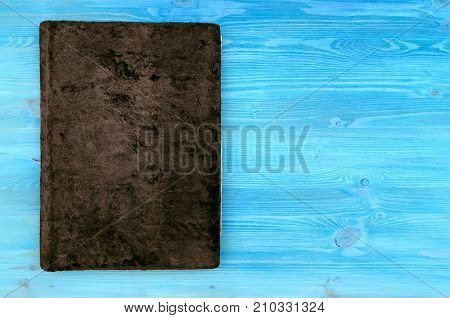 Closed bown vintage book with suede cover isolated on blue wooden table surface background. Education background with copy space.