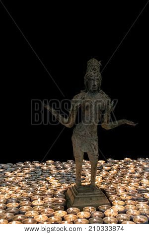 Hindu Goddess Lakshmi bronze statue by candlelight. Many candles for Deepavali Festival of Lights. Hinduism national holiday celebration image.