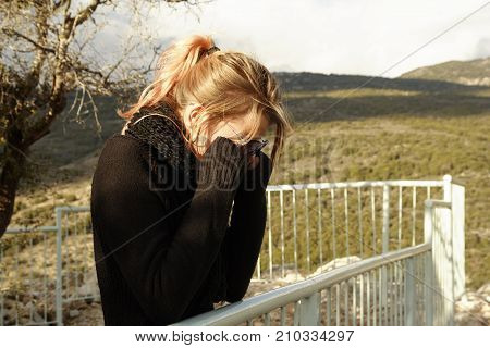 Young woman covers her eyes with hands. Standing on the mountains viewpoint