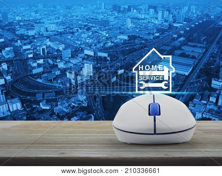 Hammer and wrench and house icon with wireless computer mouse on wooden table over city tower street and expressway Home service concept