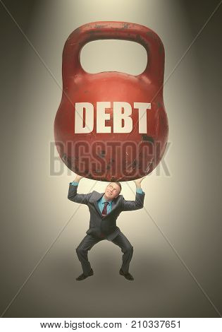 Debt. Debentures. Business man holding in his hands kettlebell above his head with DEBT inscription isolated on grey background. poster