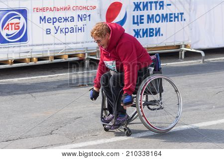 DNIPRO UKRAINE - SEPTEMBER 24 2017:Senior participant in a wheelchair hurrying to finish line during