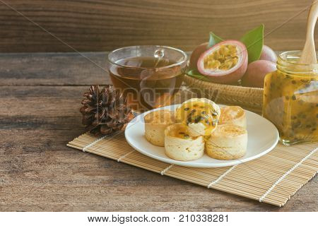 Homemade delicious plain scones serve with passion fruit jam and tea on wood table copy space for background or wallpaper. Scones is traditional English pastry for afternoon tea or coffee break. Scone and passion fruit jam ready to served.