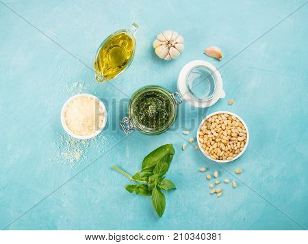 Homemade basil pesto sauce and ingredients on blue concrete background. Top wiev of basil pesto in glass jar with ingredients. Copy space. Top view or flat-lay.