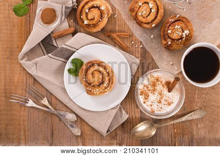 Cinnamon rolls with min and cinnamon stick on wooden table.