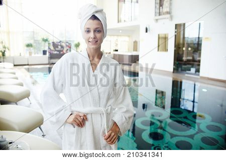 Portrait of beautiful young woman smiling at camera posing by swimming pool wearing bath robe