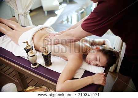 Portrait of beautiful young woman lying on massage table with eyes closed and smiling enjoying SPA treatment, man massaging her with lotions and body oils