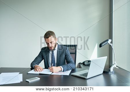 Waist-up portrait of confident young entrepreneur in classical suit taking necessary notes while preparing for important negotiations with business partners, interior of modern office on background