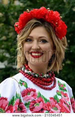 LVIV UKRAINE - 24 AUGUST 2017: Beautiful smiling Ukrainian woman in a traditional embroidered shirt with flowers on her head during the celebration of the holiday of the independence