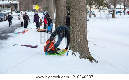 January 24 2016 Medford New Jersey: A father helps his daughter go down the sledding hill across from the Medford Library after a snow storm.