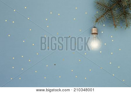 Glowing Light retro bulb on Christmas spruce. Blue holiday background with gold stars sequins. Abstract minimal New Year card. Keeping the spirit of Christmas concept