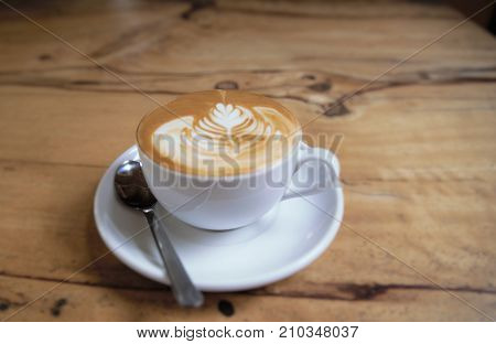 Cup of tasty cappuccino is standing on the wooden textured table. Cappuccino is in the white big cup.