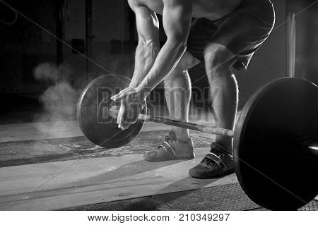Young muscular man with naked torso clapping hands with chalk powder, preparing for barbell training in gym. Power lifting equipment. Sports, fitness - healthy lifestyle concept.