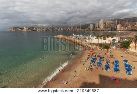 Editorial Benidorm, Spain - October 8, 2017: Holiday makers on the smallest beach in Benidorm, Mal Pas Beach, at the Spanish holiday resort of Benidorm on the eastern coast of Spain, part of the Costa Blanca