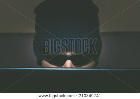 Hacker hacking confidential information on his computer while he is wearing hat and sunglasses close up