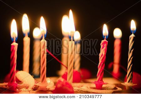 a festive cake candles are burning on the cake. Lighted candles on a cake in the dark