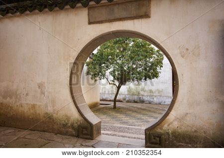 Traditional Chinese garden with a round entrance.