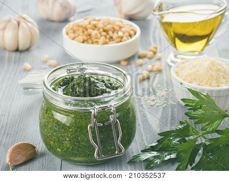 Homemade parsley pesto sauce and ingredients on gray wooden background. Close up wiev of parsley pesto in glass jar with ingredients.