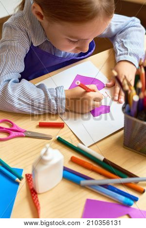 High angle portrait of adorable little girl  making gift card for mom during art and craft class in pre-school