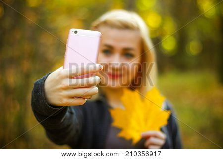 stylish modern teenage girl taking a selfie on smart phone in autumn park. Young woman smiling taking a photo of herself outside on sunny day. Woman taking self image by mobile phone in Autumn