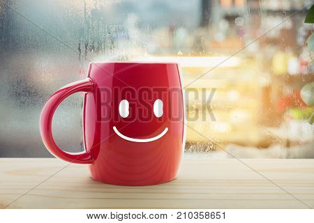 Red mug of coffee with a happy smile Steaming red coffee cup on a rainy day window background Good morning or have a happy day message concept
