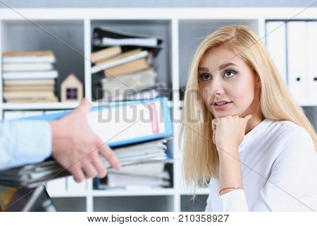 Female employee show pack of documents to busy manager or boss give extra work to executor. White collar portrait contract approval headache and depression irs lot of new problems concept