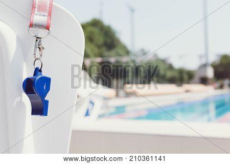 Coach whistle near outdoor swimming pool. Horizontal