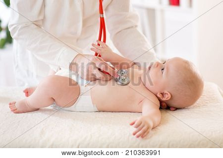 Pediatrician examines baby boy using stethoscope to listen to baby's chest checking heart beat. Child is looking at doctor